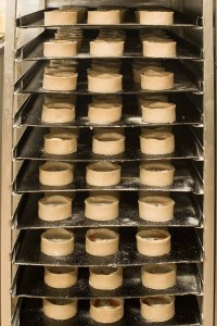 Murrays Bakers - Pies in racks ready to be baked
