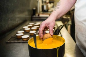 Murrays Bakery - Pineapple Cakes being dipped into the fondant